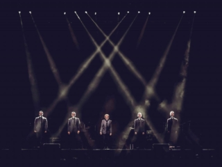 Frankie Valli with four other singers onstage in dramatic lighting