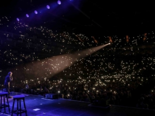 Frankie Valli onstage in an arena with lighters up